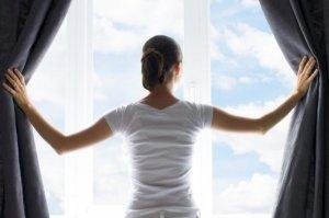 白い服の女性がカーテンを開ける様子