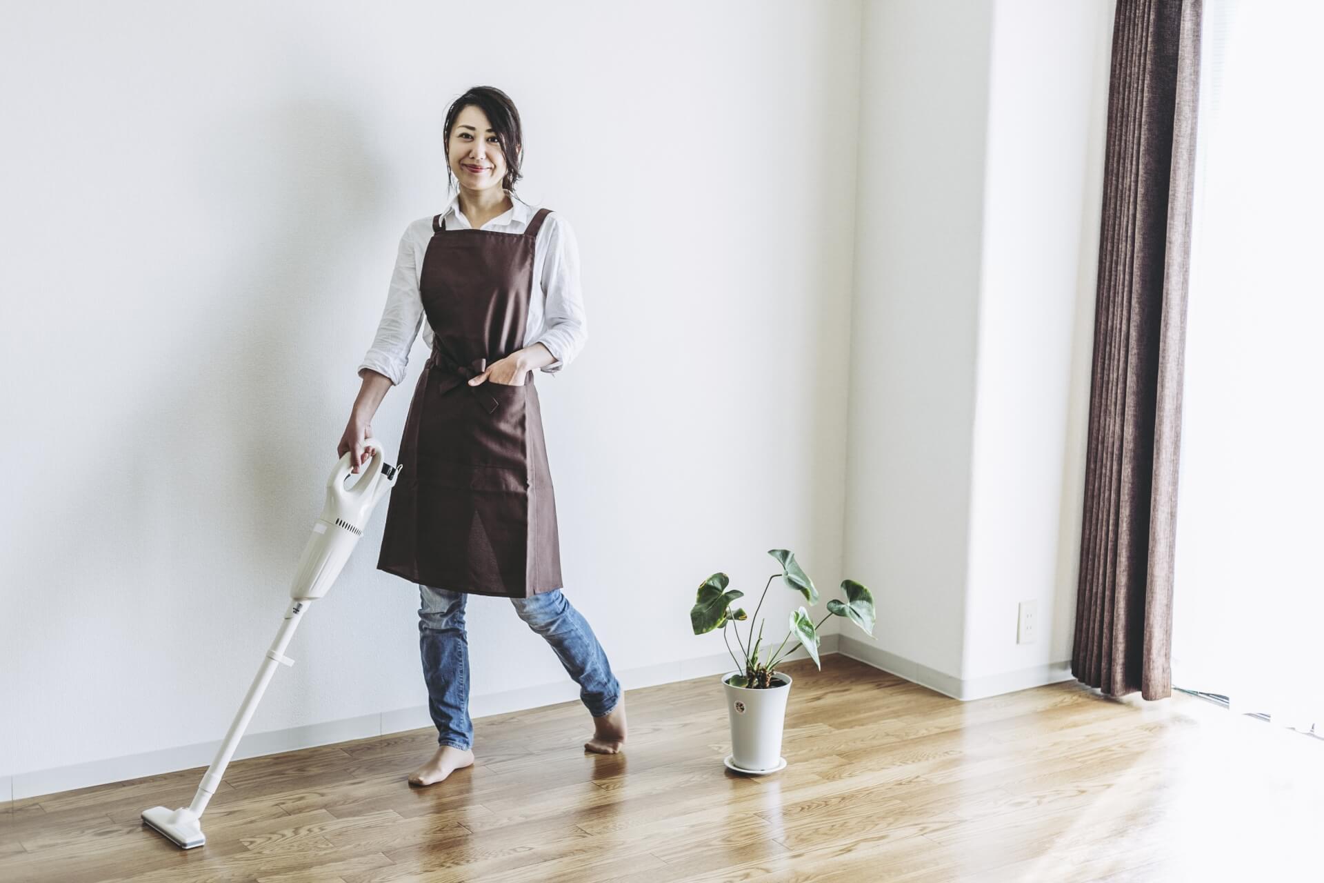 一人暮らしの女性と縦型掃除機