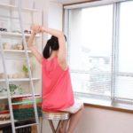 ピンクの服を着た背伸びする後ろ姿の女性