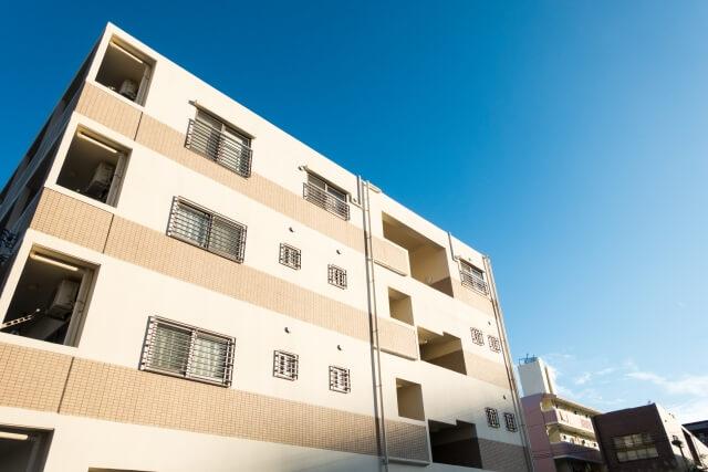 3階建てのマンションと青い空