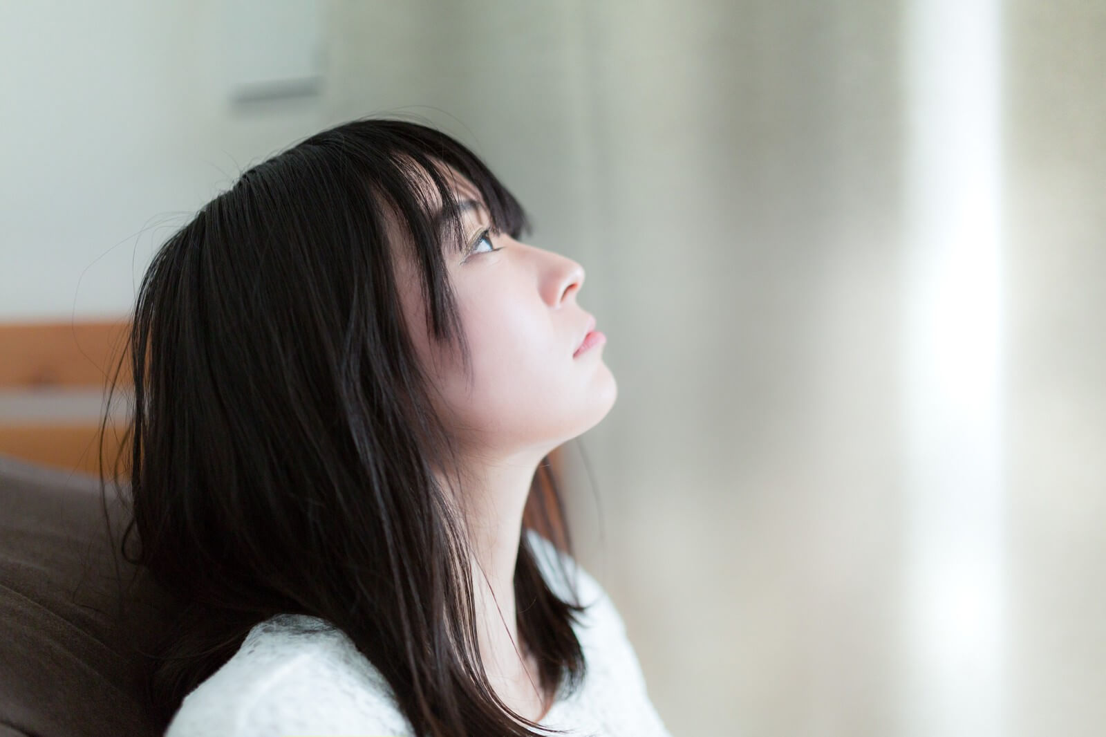 1人暮らしで上を見て考える女性