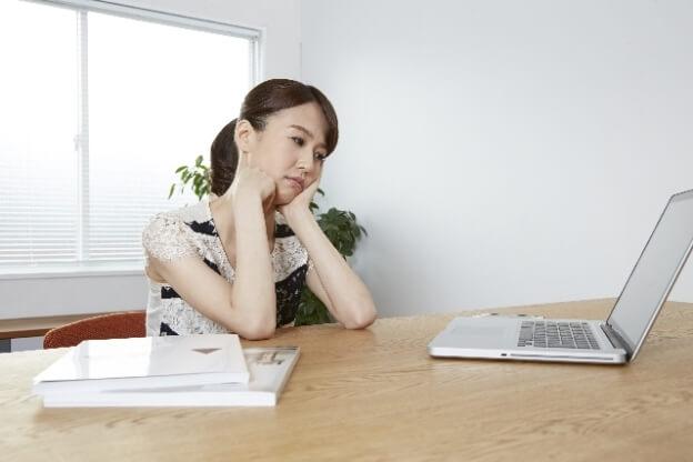 髪を縛った女性が両手をついてパソコンを見ながら考えている