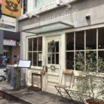 白の壁窓が2つと椅子と緑のあるカフェ