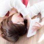 床に寝ながら本を読んでいる