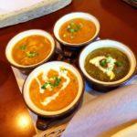 茶色のテーブルの上にある4種類のインドカレー
