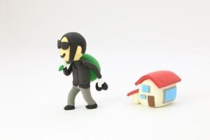 黒い服の泥棒と赤い屋根の家
