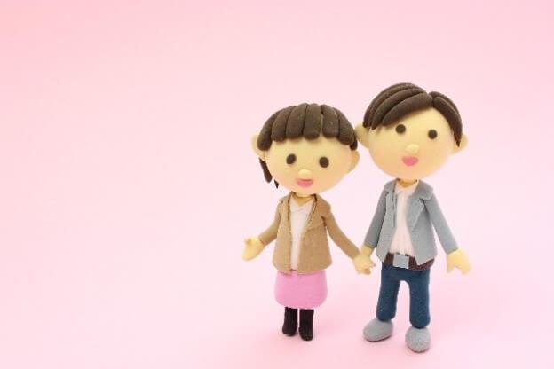 背景がピンクで女性と男性が手を繋いでいる