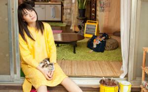 黄色の服の女性がガラスに寄りかかって猫を抱いている